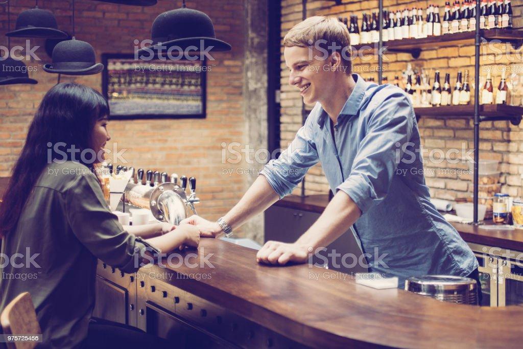 Lächelnde Barkeeper im Gespräch mit Kunden am Schalter - Lizenzfrei Alkoholismus Stock-Foto