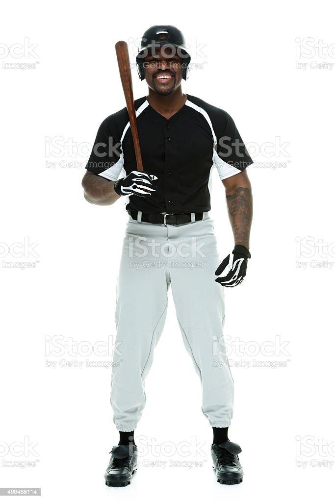 Smiling baseball player holding bat stock photo