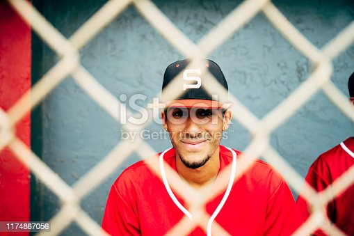 Relaxed and smiling Hispanic baseball player photographed through fence while sitting in dugout with teammates.
