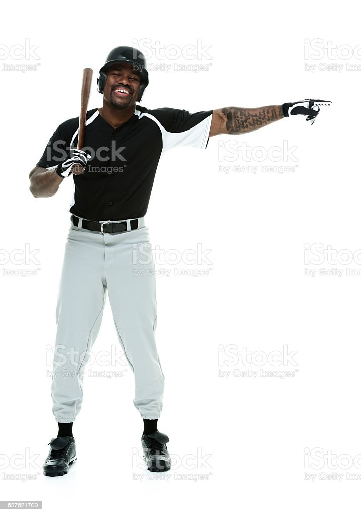 Smiling baseball player pointing away stock photo