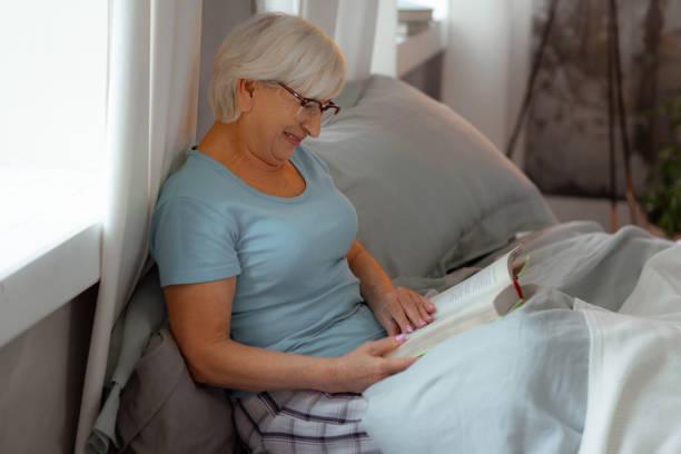 lächelnd strahlende dame, die ein buch im bett liest. - sexy granny stock-fotos und bilder