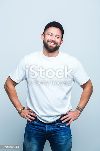 Portrait of smiling beard man with hands on hips on white background.