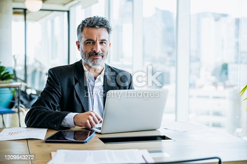 Buenos Aires businessman sitting at office work table next to window with view of downtown and pausing from typing on laptop to smile at camera.