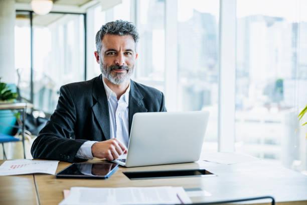 uomo d'affari barbuto sorridente che lavora su laptop in ufficio - business man foto e immagini stock