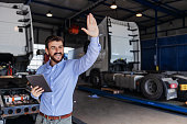istock Smiling bearded chief standing in garage of shipping firm, holding tablet and waving. In background are trucks. 1284732651
