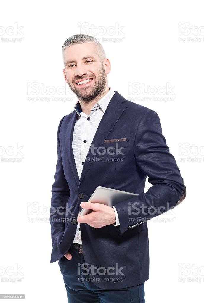 Smiling bearded grey hair elegant businessman holding digital tablet Portrait of elegant bearded grey hair businessman wearing suit, holding a digital tablet in hand, smiling at camera. Studio shot, one person, isolated on white. Adult Stock Photo