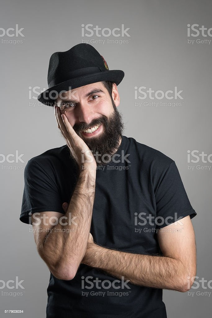 d65efadd0cb Smiling Bearded Hipster Wearing Hat With Head Resting On Hand Stock ...
