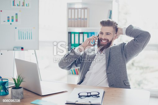 513583458 istock photo Smiling bearded man in formalwear  having a talk with his business partners while sitting at office, hs a stylish hairdo, toothy smile 936098208