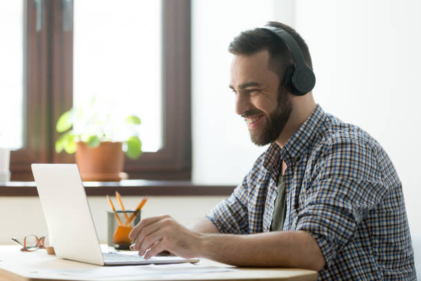 Smiling bearded man in headphones looking on laptop and typing stock photo