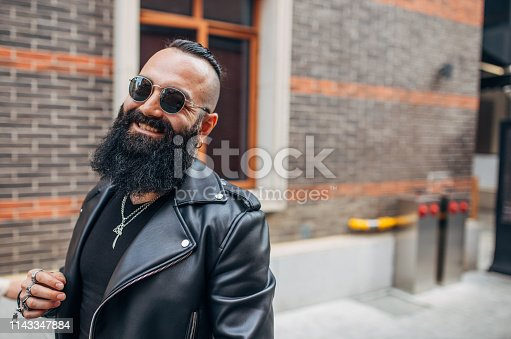 Bearded man wearing leather jacket and sunglasses, standing on the street and smiling.