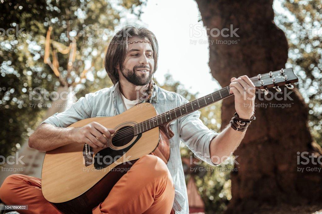 Sorrindo homem barbado cantando músicas tocando guitarra - foto de acervo