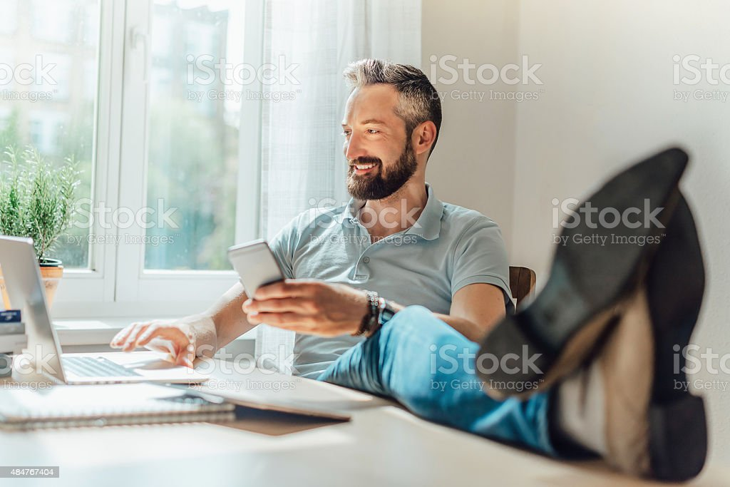 smiling bearded man trading online stock photo