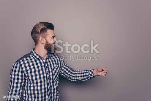 636829300 istock photo Smiling bearded man with raised fist on gray background 931449404