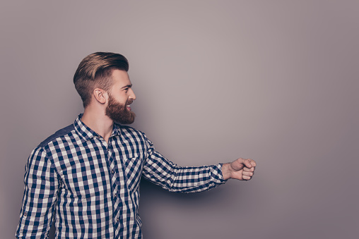 636829368 istock photo Smiling bearded man with raised fist on gray background 931449404