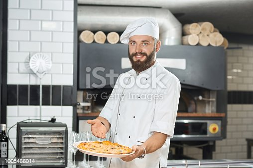 istock Smiling bearded pizzaiolo holding fresh baked mouthwatering pizza. 1005466014