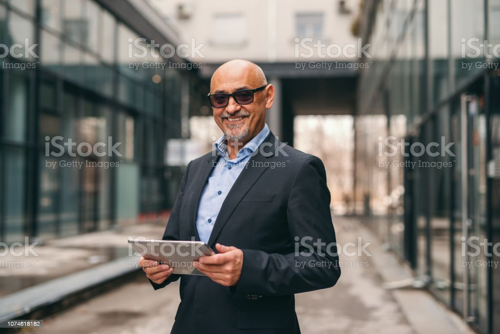 Smiling bearded senior in suit holding tablet while standing outdoors. stock photo