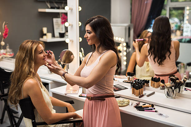 smiling beautician applying blush on young woman in beauty salon. - makeup artist bildbanksfoton och bilder