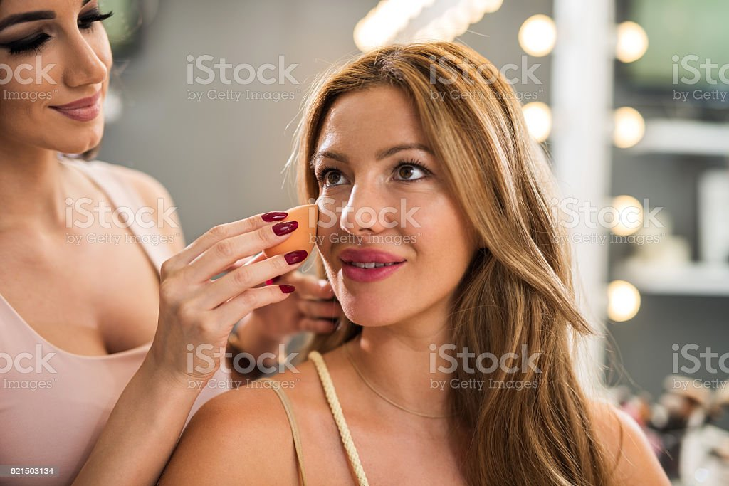 Smiling beautician applying face powder on beautiful woman. foto stock royalty-free