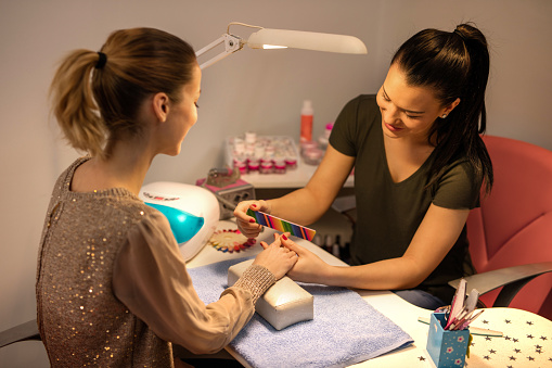 Smiling beautician doing woman's nails at nail salon. stock photo