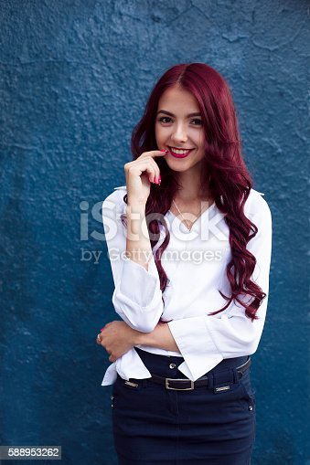 A beauty shot, photo, picture of a young, smiling, laughing, crazy, full of fun and joy dark eyed woman, girl with her red, perfect healthy skin standing on the blue background, looking at camera. Glamor portrait of a sexy woman with red hair on blue background. Portrait of happy smiling red-haired, redhead girl in white blouse and blue skirt.