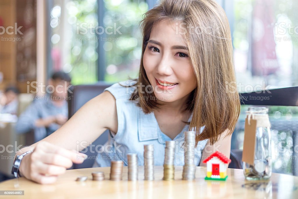 smiling beautiful asian woman stacking gold coins stock photo