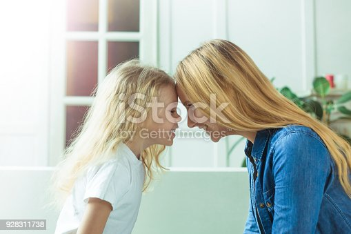 641288086 istock photo Smiling beautiful blond mother and daughter touch their foreheads on each other sitting on the couch at home 928311738