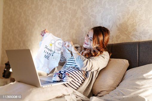 Smiling beautiful brunette having video call over the laptop. Woman showing baby clothes she bought. Evening time.