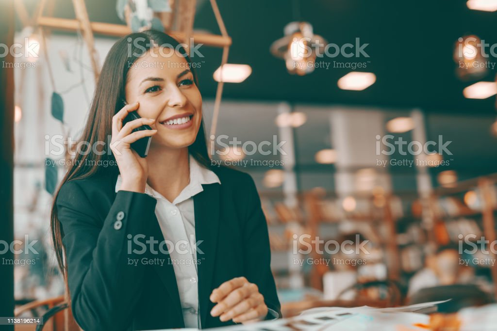 Smiling beautiful brunette in formal wear using smart phone for...