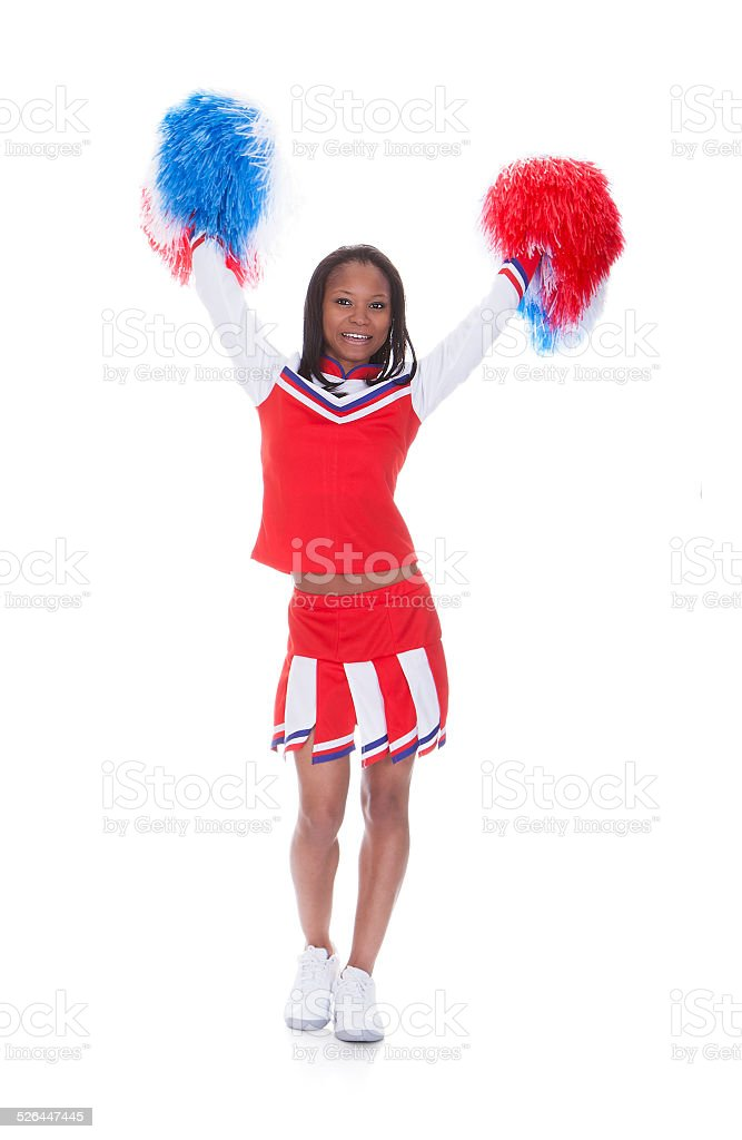 Smiling beautiful cheerleader with pompoms. stock photo
