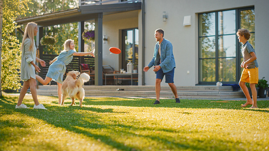Smiling Beautiful Family of Four Play Fetch flying disc with Happy Golden Retriever Dog on the Backyard Lawn. Idyllic Family Has Fun with Loyal Pedigree Dog Outdoors in Summer House Backyard