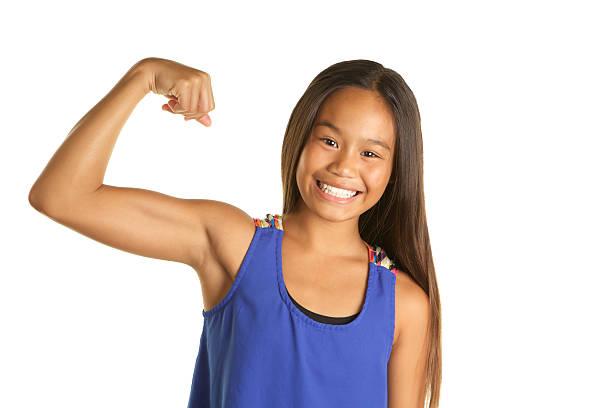 Smiling Beautiful Filipino Girl Making a Muscle on White Background stock photo