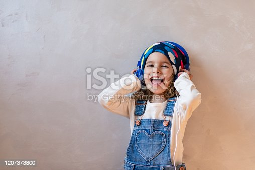 Happy smiling child enjoys listening to music on headphones.