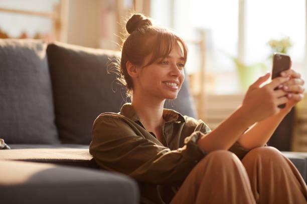 Lächeln schöne Mädchen mit Pony auf sofa lehnen und Surfen Internet auf dem Smartphone, während der Suche nach Informationen – Foto