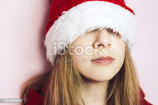 Smiling beautiful girl with long blonde hair in fluffy Santa Claus hat on a pink background. Teenage girl pulled her hat over her eyes