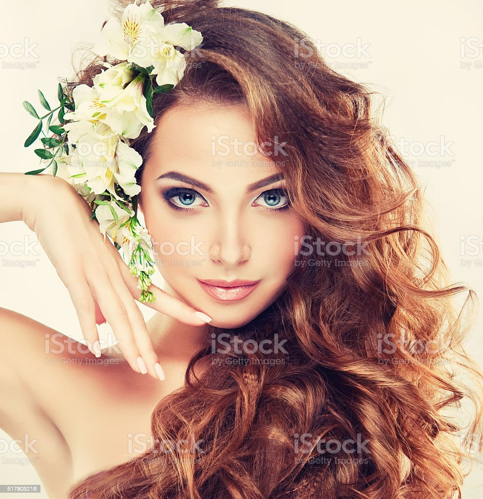 Smiling Beautiful girl.Delicate pastel flowers in curly hair. stock photo