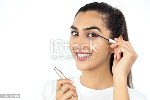 istock Smiling Beautiful Indian Lady Applying Mascara 640183536