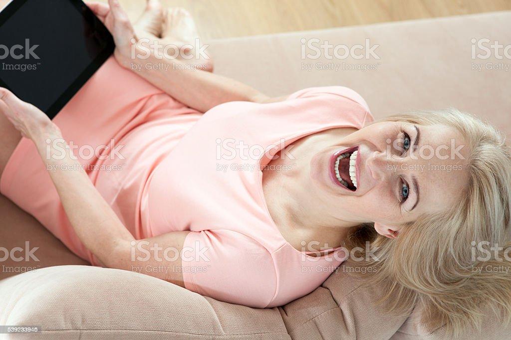 Sonriendo hermosa mediana edad mujer sentada en un sofá con una mesa foto de stock libre de derechos