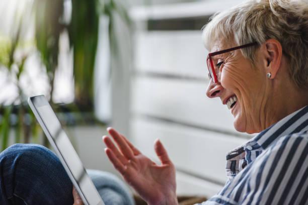 Lächelnde schöne Seniorin mit digitalen Tablet zu Hause – Foto