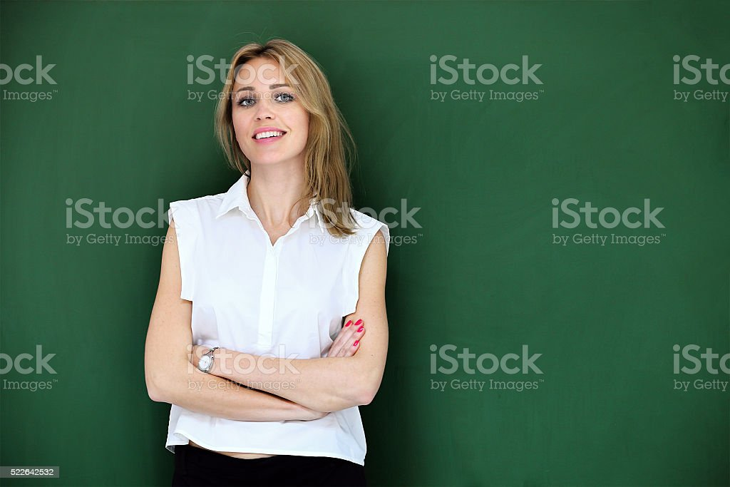 Smiling beautiful teacher at blackboard stock photo