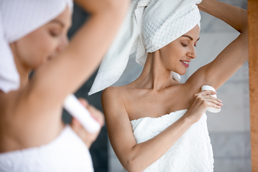Smiling beautiful woman applying antiperspirant to armpit after shower close up, standing in front of mirror in bathroom, pretty young female wearing white bath towel on head using stick deodorant