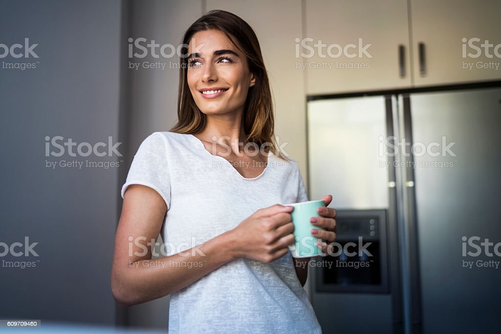 Smiling beautiful woman having coffee at home - Photo