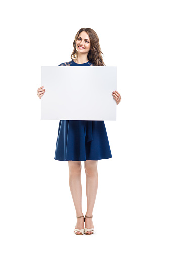 Smiling beautiful woman holding empty sign board isolated on white background. Full length portrait