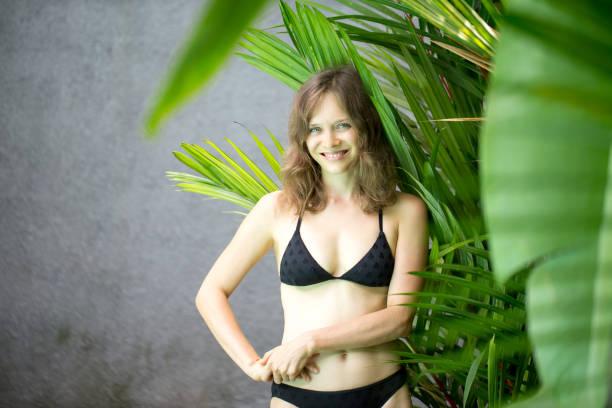 Smiling Beautiful Woman in Bikini at Tropical Plant stock photo