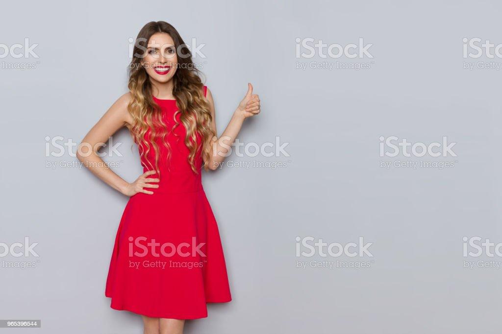 微笑美麗的女人穿著紅色的禮服顯示拇指 - 免版稅一個人圖庫照片