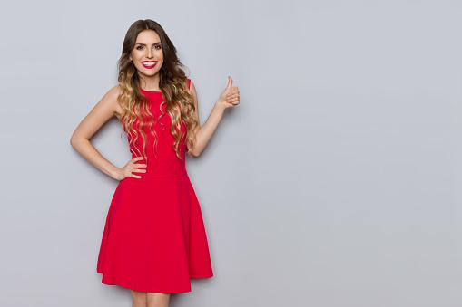 微笑美麗的女人穿著紅色的禮服顯示拇指 照片檔及更多 一個人 照片