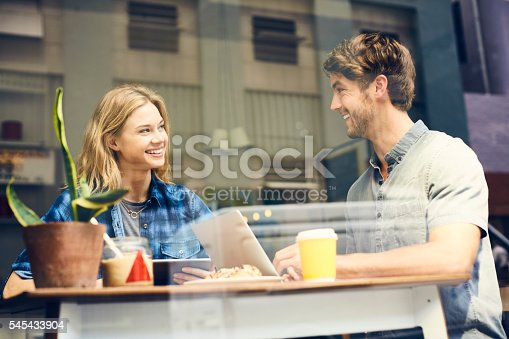 Smiling woman looking at man in coffee shop. Male and female are using technologies at table. They are in trendy casuals seen through glass.