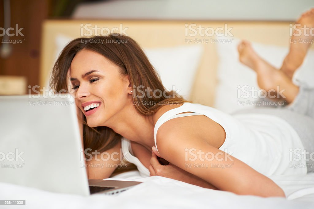 Smiling beautiful woman lying on bed in front of laptop Beautiful young woman relaxing on her bed in white casual undershirt using laptop 2015 Stock Photo