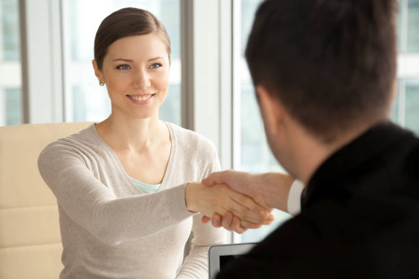 Femme belle souriante serrer la main de sexe masculin, en arrivant à l'entretien d'embauche - Photo