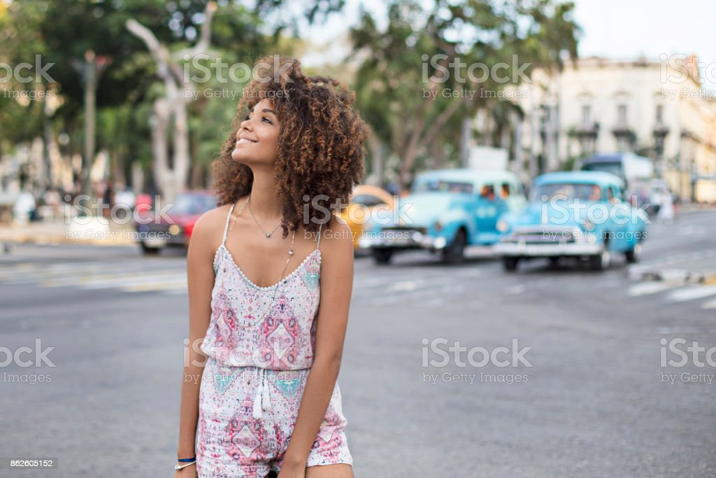 Smiling beautiful woman standing on street in city stock photo