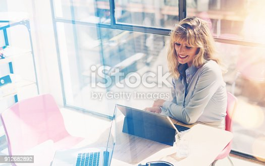 istock Smiling beautiful woman working at the modern office loft.Coworker using electronic touch tablet computer on workplace.Horizontal. Blurred background. 912682892